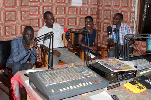 Evelyn Ayebare, right, tells her story on a local radio station in Uganda.